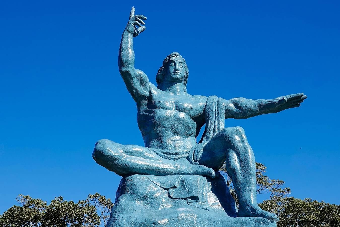 Japan, Nagasaki, Friedenspark, Statue des Friedens, Die erhobene rechte Hand bedeutet die Bedrohung der Atomwaffen, während der linke ausgestreckte Arm den Wunsch nach Frieden repräsentiert und die Augen sind im Gebet für die Seelen der Atombombenopfer geschlossen